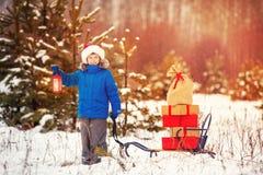Le petit garçon mignon dans le chapeau de Santa porte un traîneau en bois avec des cadeaux dans la forêt neigeuse Images stock