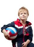 Le petit garçon mignon dans une salopette retient un volleyba Images stock
