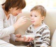 Le petit garçon mignon est alimenté utilisant la cuillère Photos stock