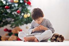 Le petit garçon mignon et son singe jouent, jouant sur le comprimé Image stock