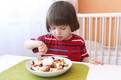 Le petit garçon mignon mange de la salade de fruits photographie stock
