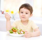 Le petit garçon mignon mange de la salade végétale Image libre de droits