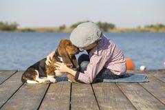 Le petit garçon mignon s'assied par la rivière avec son chien Images stock