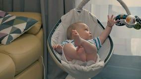 Le petit garçon mignon se situe dans le berceau moderne et joue avec le jouet clips vidéos