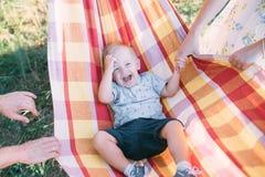 Le petit garçon mignon se situe dans un hamac et a l'amusement image libre de droits
