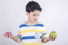 Le petit garçon ne veut pas manger du fruit image stock