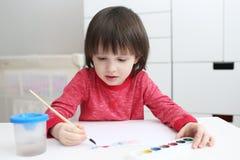Le petit garçon peint avec l'aquarelle à la maison Photographie stock