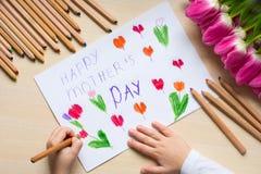 Le petit garçon peint la carte de voeux pour la maman le jour du ` s de mère avec le ` heureux de jour du ` s de mère de ` d'insc Image stock