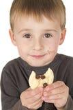 Le petit garçon a plaisir à manger le biscuit Photographie stock