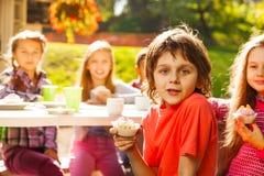 Le petit garçon positif tient le petit gâteau avec ses amis Image stock