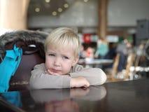 Le petit garçon réfléchi s'assied à une table reposant son menton sur les ses FO Images stock