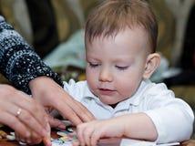 Le petit garçon rassemble des puzzles photographie stock