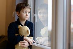 Le petit garçon regarde la fenêtre Images libres de droits