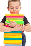 Le petit garçon retient une pile de livres Image libre de droits