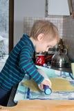 Le petit garçon roule la pâte photo stock