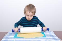 Le petit garçon roule la pâte photo libre de droits