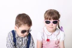 Le petit garçon sérieux et la fille de sourire s'asseyent dans des lunettes de soleil Photo stock