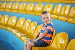 Le petit garçon s'asseyant dans un stade vide parmi en plastique jaune engourdissent Image libre de droits