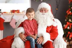 Le petit garçon s'asseyant sur le ` authentique de Santa Claus enroulent à l'intérieur image libre de droits