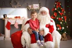 Le petit garçon s'asseyant sur le ` authentique de Santa Claus enroulent à l'intérieur photo libre de droits