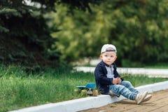 Le petit garçon s'asseyent au fond de vert de tache floue Photos stock