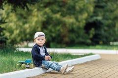 Le petit garçon s'asseyent au fond de vert de tache floue Images stock