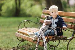 Le petit garçon s'asseyent sur le banc avec son jouet Images stock