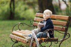 Le petit garçon s'asseyent sur le banc avec son jouet Photographie stock