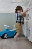 Le petit garçon s'asseyent sur une voiture de jouet Images stock