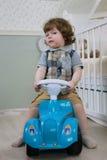 Le petit garçon s'asseyent sur une voiture de jouet Photo libre de droits