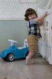Le petit garçon s'asseyent sur une voiture de jouet Photographie stock libre de droits