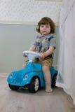 Le petit garçon s'asseyent sur une voiture de jouet Image libre de droits