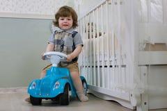 Le petit garçon s'asseyent sur une voiture de jouet Photographie stock