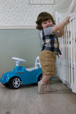 Le petit garçon s'asseyent sur une voiture de jouet Photos stock