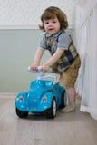 Le petit garçon s'asseyent sur une voiture de jouet Images libres de droits