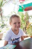 Le petit garçon s'assied à une table à côté d'un livre et d'un sourire image stock