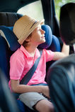 Le petit garçon s'assied dans le siège de sécurité Image stock