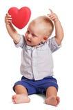 Le petit garçon s'assied, son coeur de rouge de prise de mains Image libre de droits