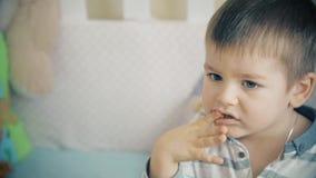 Le petit garçon s'assied sur le lit et mange les bâtons doux délicieux banque de vidéos
