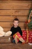 Le petit garçon s'assied sur un plancher en bois près d'un arbre de Noël photographie stock