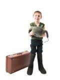Le petit garçon sans abri se tenant dans des bottes de feutre à côté d'une valise et prie pour l'aumône se tenant dans le chapeau images libres de droits