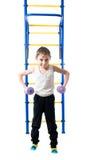 Le petit garçon se tient à côté des escaliers et des barres horizontales et se tient dans l'haltère de mains Photo libre de droits