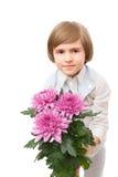 Le petit garçon se tient avec un bouquet de marguerite des prés lilas Images stock