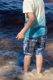 Le petit garçon se tient avec un filet de pêche directement en mer Images libres de droits