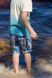 Le petit garçon se tient avec un filet de pêche directement en mer Image stock