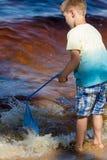 Le petit garçon se tient avec un filet de pêche directement en mer Photos stock