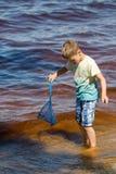 Le petit garçon se tient avec un filet de pêche directement en mer Photographie stock