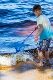 Le petit garçon se tient avec un filet de pêche directement en mer Images stock