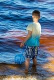 Le petit garçon se tient avec un filet de pêche directement en mer Photos libres de droits