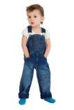 Le petit garçon se tient dans des combinaisons de jeans Photo libre de droits